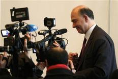 France's Finance Minister Pierre Moscovici is surrounded by journalists as he leaves after a news conference at the Economy Ministry in Paris December 19, 2012. REUTERS/Charles Platiau