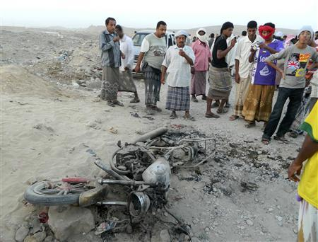 People gather around a motorcycle destroyed in a drone strike near al-Sheher town of Yemen's eastern region of Hadramout December 28, 2012. REUTERS/Stringer