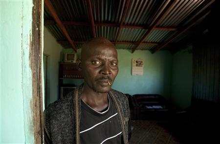 Former gold miner Thulani Bitsha, 39, stands in the doorway to his home near Bizana in South Africa's impoverished Eastern Cape province in this March 7, 2012 file photo. Bitsha worked underground in the country's gold mines for 13 years before being diagnosed with silicosis, a debilitating lung disease. REUTERS/Mike Hutchings/Files