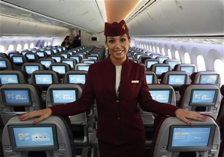 An air stewardess for Qatar Airways poses in the economy class cabin of the new Boeing 787 Dreamliner at the Farnborough Airshow 2012 in southern England July 10, 2012. REUTERS/Luke MacGregor/Files