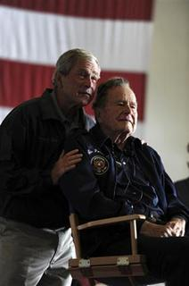 Former Presidents George W. Bush, (L) and George H.W. Bush deliver remarks to the crew during a ceremony aboard the aircraft carrier USS George H.W. Bush (CVN 77) during a promotion and reenlistment ceremony in the Atlantic Ocean in this June 10, 2012 handout photo handout photo obtained by Reuters June 11, 2012. REUTERS/Joshua D. Sheppard/U.S. Navy/Handout/Files
