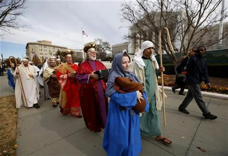 Actors dressed as Mary and Joseph carrying a baby representing Jesus lead other actors portraying the Three Wise Men as part of a nativity scene past the Supreme Court in Washington, December 5, 2012. REUTERS/Jason Reed