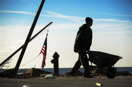 Contractor Chris Siller pushes a wheelbarrow full of sand to fill in a lawn damaged by superstorm Sandy two months after the storm caused extensive damage in the Queens borough region of Belle Harbor, New York, December 28, 2012. REUTERS/Lucas Jackson