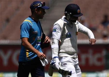 Sri Lanka's Kumar Sangakkara (R) looks at his injured finger as he walks off the ground with a team trainer retired hurt during the third day of the second cricket test against Australia at the Melbourne Cricket Ground December 28, 2012. REUTERS/David Gray