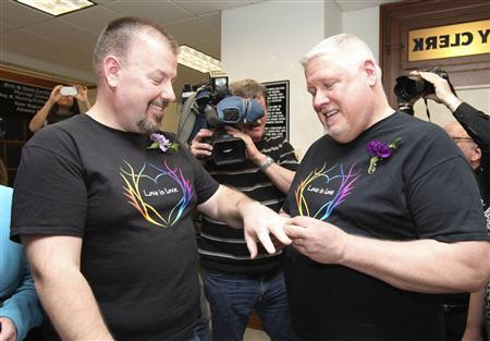 Same-sex couple Steven Bridges (L) and Michael Snell exchange rings after filling out a marriage license at the City Hall in Portland, Maine December 29, 2012. REUTERS/Joel Page