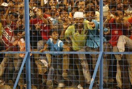 Soccer fans watch Bayern Munich team captain and goalkeeper Oliver Kahn's felicitation ceremony during an exhibition match against Mohun Bagan at Salt Lake Stadium, in Kolkata, May 27, 2008. REUTERS/Jayanta Shaw/Files