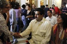 El vicepresidente venezolano, Nicolás Maduro, dijo el viernes que el sábado partirá a Cuba para visitar al presidente Hugo Chávez, pero no ofreció detalles sobre la salud del mandatario que fue sometido a una delicada intervención quirúrgica para tratar el cáncer que padece. En la imagen, Maduro (centro) saluda a un simpatizante en una misa por la salud de Chávez en Caracas el 24 de diciembre. REUTERS/Carlos Garcia Rawlins
