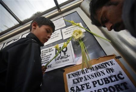 Demonstrators put flowers on the billboard of a bus stop during a protest march in New Delhi December 29, 2012. REUTERS/Danish Siddiqui