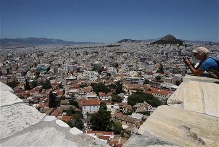A tourist takes photographs at the Acropolis hill overlooking Athens, July 10, 2011. REUTERS/John Kolesidis