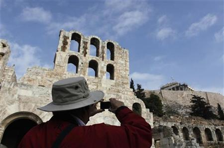 A man takes photographs of the Parthenon temple as he stands outside the ancient Herodes Atticus theatre in Athens November 27, 2012. REUTERS/John Kolesidis