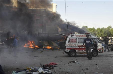 A rescuer (R) walks near an ambulance after a bomb explosion in a bus, in Cantonment area, Karachi December 29, 2012. A bomb went off on a bus in the southern Pakistani city of Karachi on Saturday killing six people and wounding 48, police and a hospital official said. REUTERS/Stringer