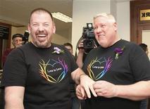 Las primeras parejas de gays y lesbianas en casarse bajo la nueva ley de Maine de matrimonio homosexual sexo intercambiaron votos el sábado en una serie de ceremonias civiles celebradas poco después de la medianoche. Imagen de Steven Bridges (izq.) y Michael Snell al intercambiarse los anillos en la ceremonia celebrada el 29 de diciembre en el ayuntamiento de Portland, en Maine. REUTERS/Joel Page