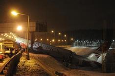Destroços de avião são vistos em rodovia próximo ao aeroporto de Vnukovo, Rússia. Um avião russo se partir em pedaços depois de derrapar da pista e bater em uma rodovia nos arredores de Moscou neste sábado, matando quatro de 12 pessoas a bordo e formando nuvens de fumaça na rodovia congelada. 29/12/2012 REUTERS/Maxim Shemetov