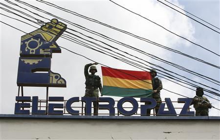Bolivian police officers hold a Bolivian flag on the roof of the headquarters of electricity distribution company Electropaz, a subsidiary of the Spanish energy company Iberdrola, after President Evo Morales announced their nationalization in La Paz, December 29, 2012. REUTERS/Gaston Brito