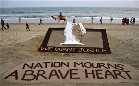 People walk near a sand sculpture with the words ''We Want Justice'' created by Indian sand artist Sudarshan Patnaik, in solidarity with a gang rape victim who was assaulted in New Delhi, on a beach in the eastern Indian state of Odisha December 29, 2012. A woman whose gang rape provoked protests and a rare national debate about violence against women in India died from her injuries on Saturday, prompting promises of action from government that has struggled to respond to public outrage. REUTERS/Stringer