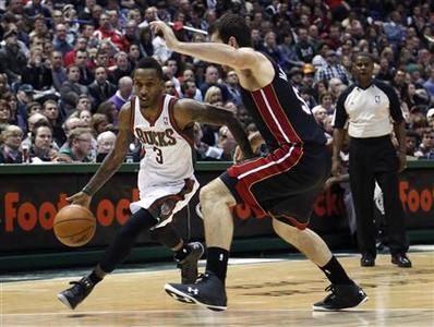 Milwaukee Bucks guard Brandon Jennings (L) drives to the basket against Miami Heat center Josh Harrellson in the second half of their NBA basketball game in Milwaukee, Wisconsin December 29, 2012. REUTERS/Darren Hauck