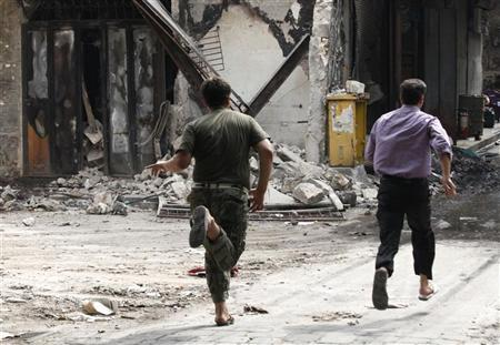 A Free Syrian Army fighter and a civilian run to take cover from a sniper loyal to Syria's President Bashar al-Assad in Bab al-Naser district in Old Aleppo October 2, 2012. REUTERS/Zain Karam