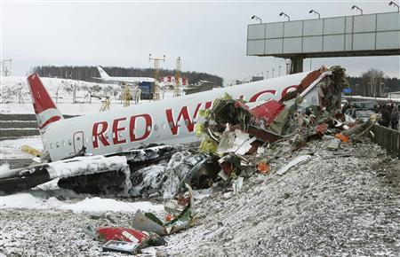 An aircraft wreckage lies next to a highway near Moscow's Vnukovo Airport December 30, 2012. A Russian airliner flying without passengers broke into pieces after it slid off the runway and crashed onto a highway outside Moscow upon landing on Saturday, killing four of the eight crew on board and leaving smoking chunks of fuselage on the icy road. REUTERS/Mikhail Voskresensky