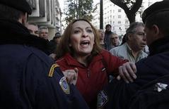 Más de dos tercios de los griegos dice que su Gobierno no está combatiendo la evasión fiscal, según un sondeo divulgado el sábado, un tema que se ha convertido en un importante foco de descontento social que se suma al descontento popular por las duras medidas de austeridad impuestas a Atenas por su plan de rescate. En la imagen del 20 de diciembre, una tenedora de bonos grita al primer ministro, Antonis Samaras (al que no se ve) al dejar la Oficina de Contabilidad General del Estado en Atenas. REUTERS/John Kolesidis
