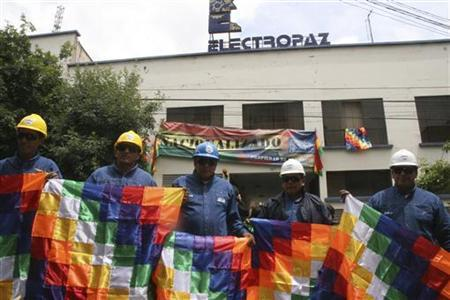 Workers of electricity distribution company Electropaz, a subsidiary of the Spanish energy company Iberdrola, hold ''Whiphalas'' (indigenous flag), in La Paz, December 29, 2012. Bolivia nationalized two electricity distribution companies owned by Spanish utility Iberdrola, according to a decree announced by President Evo Morales on Saturday and aimed at enhancing rural energy services. The former parent company will be compensated according to a valuation to be drawn up by an independent arbiter, Morales said. The left-wing leader has also nationalized oil, telecommunications and electrical generation companies. REUTERS/Jose Lirauze/Bolivian Presidency/Handout (BOLIVIA - Tags: POLITICS ENERGY CIVIL UNREST BUSINESS) FOR EDITORIAL USE ONLY. NOT FOR SALE FOR MARKETING OR ADVERTISING CAMPAIGNS. THIS IMAGE HAS BEEN SUPPLIED BY A THIRD PARTY. IT IS DISTRIBUTED, EXACTLY AS RECEIVED BY REUTERS, AS A SERVICE TO CLIENTS