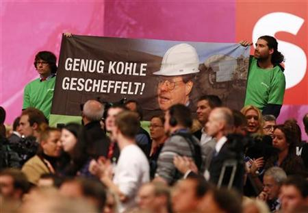 Demonstrators hold a placard reading 'You made enough money' during the speech of top candidate of the German Social Democratic Party (SPD) for the 2013 German general elections, Peer Steinbrueck during the extraordinary party meeting of the SPD in Hanover, December 9, 2012. REUTERS/Ralph Orlowski(GERMANY - Tags: POLITICS)
