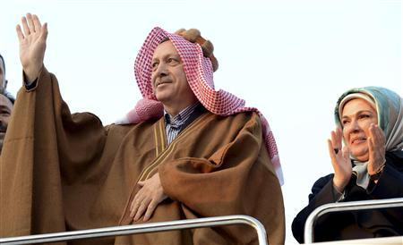 Turkish Prime Minister Tayyip Erdogan, in traditional clothes, greets Syrian refugees with his wife Emine Erdogan as they visit a refugee camp near Akcakale border crossing on the Turkish-Syrian border, southern Sanliurfa province, December 30, 2012. REUTERS/Kayhan Ozer/Prime Minister's Press Office/Handout