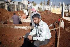 Homem senta-se enquanto outros cavam covas para futuras vítimas do conflito civil na Síria no cemitério Sheikh Saeed na cidade de Azaz, Síria. Coveiros de cemitério da cidade de Azaz, no norte da Síria, não esperam mais bombas caírem para começarem a cavar. Os mortos chegam muito rápido. 30/12/2012 REUTERS/Ahmed Jadallah