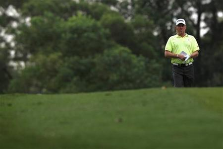 Miguel Angel Jimenez of Spain walks on the 18th fairway during the third day of the Hong Kong Open golf tournament November 17, 2012. REUTERS/Tyrone Siu/Files