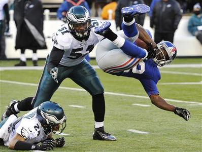 New York Giants David Wilson (R) is tackled by Philadelphia Eagles Nnamdi Asomugha (L) and Jamar Chaney (C) in the third quarter of their NFL football game in East Rutherford, New Jersey, December 30, 2012. REUTERS/Ray Stubblebine