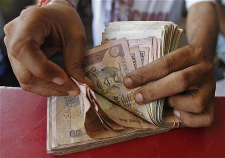 A grocery shop owner counts rupees notes in the western Indian city of Ahmedabad May 23, 2012. REUTERS/Amit Dave/Files