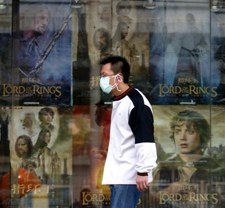 A masked Chinese man walks past a cinema in Beijing April 27, 2003. REUTERS/Wilson Chu/Files