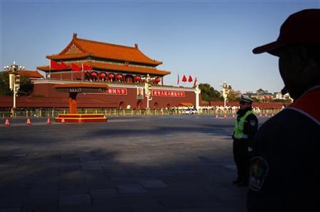 A policeman and traffic warden look over a vacant main road that runs through Beijing's Tiananmen Square November 13, 2012. REUTERS/David Gray/Files