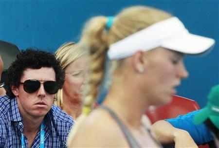 Golfer Rory McIlroy of Northern Ireland watches as his girlfriend Caroline Wozniacki (R) of Denmark plays Ksenia Pervak of Kazakhstan during their women's singles match at the Brisbane International tennis tournament in Brisbane December 31, 2012. REUTERS/Daniel Munoz