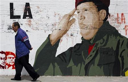 A man walks past a mural depicting Venezuelan President Hugo Chavez in Caracas December 30, 2012. Venezuelan Vice President Nicolas Maduro, who arrived on Saturday in Havana, said it is the ''right time'' to visit Chavez, the first time he would see him since the president went through his fourth surgery for cancer, according to Cuban media reports. REUTERS/Carlos Garcia Rawlins (VENEZUELA - Tags: POLITICS HEALTH TPX IMAGES OF THE DAY)