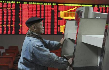 An investor looks at a computer screen in front of an electronic board showing stock information at a brokerage house in Hefei, Anhui province December 25, 2012. REUTERS/Stringer (CHINA - Tags: BUSINESS)