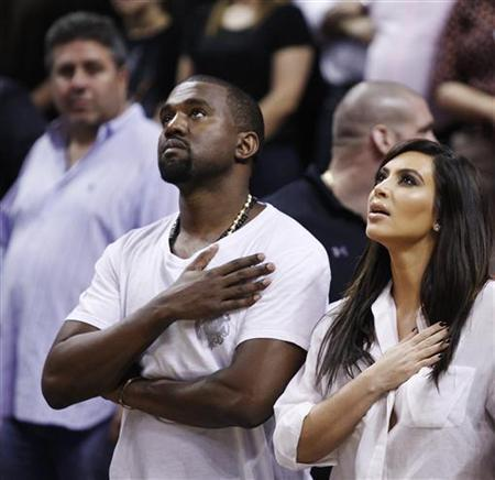 Rap musician Kanye West is seen court side with reality television star Kim Kardashian during the national anthem before the Miami Heat played the New York Knicks in their NBA basketball game in Miami, Florida December 6, 2012. REUTERS/Andrew Innerarity