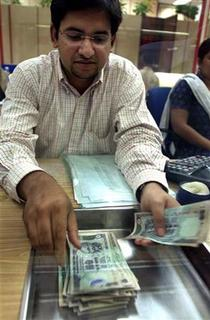 An Indian forex dealer counts rupee notes during busy market hours in a foreign exchange firm in Mumbai March 31, 2004. REUTERS/Punit Paranjpe/Files