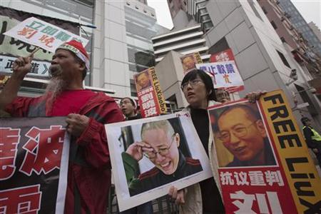 Pro-democracy protesters hold signs and posters of Chinese Nobel Peace Prize laureate Liu Xiaobo (R) and his wife Liu Xia (C) during a protest outside the Chinese liaison office in Hong Kong December 25, 2012. REUTERS/Tyrone Siu