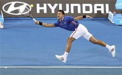 El campeón del Abierto de Australia Novak Djokovic sufrió un susto y casi se lesiona el lunes en la Copa Hopman cuando el número uno del mundo se dañó la pierna mientras sus fans le empujaban cuando firmaba autógrafos. En la imagen, Djokovic y Ana Ivanovic durante el partido ante los italianos Andreas Seppi y Francesca Schiavone en la Copa Hopman, en Perth, el 31 de diciembre de 2012. REUTERS/Stringer
