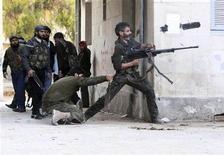 Rebeldes sírios enfrentam forças leais ao presidente Bashar al-Assad no distrito de Bustan al-Qasr, em Aleppo. 30/12/2012. REUTERS/Muzaffar Salman