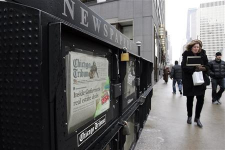 People walk past a newspaper box across from the Chicago Tribune tower in Chicago, Illinois December 8, 2008. Publisher and broadcaster Tribune Co., a privately held company, which publishes the Chicago Tribune and the Los Angeles Times has filed for Chapter 11 bankruptcy protection according to the Los Angeles Times December 8. REUTERS/Frank Polich
