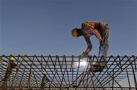 A worker welds iron rods at the construction site of a commercial complex in the western Indian city of Ahmedabad November 29, 2012. REUTERS/Amit Dave
