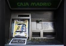 """La Sociedad de Gestión de Activos procedentes de la Reestructuración Bancaria (Sareb), conocido como """"banco malo"""", dijo que ha iniciado el lunes su andadura al asumir los activos inmobiliarios tóxicos procedentes de los bancos nacionalizados por un importe conjunto de 36.695 millones de euros. En la imagen, una pegatina en un cajero automático de Bankia-Caja Madrid, en Madrid, el 16 de junio de 2012. REUTERS/Susana Vera"""
