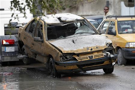 A destroyed vehicle is towed from the site of a bomb attack in Baghdad's Karrada district, December 31, 2012. REUTERS/Saad Shalash