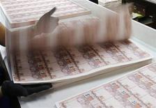 Imagen de archivo de un empleado de la Casa de Moneda de Brasil durante la revisión de billetes en Río de Janeiro, ago 23 2012. Analistas anticiparon, por primera vez en un año, que la economía brasileña crecerá menos de un 1 por ciento en 2012 y, al mismo tiempo, elevaron por cuarta semana consecutiva sus pronósticos de inflación (IPCA) para el año, según un sondeo del banco central publicado el lunes. REUTERS/Sergio Moraes
