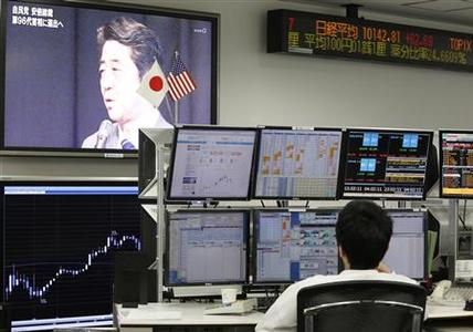 An employee of a foreign exchange trading company looks at monitors as a television set shows Japan's incoming Prime Minister and the leader of Liberal Democratic Party (LDP) Shinzo Abe speaking in Tokyo December 26, 2012. The yen fell to a 20-month low against the dollar on Wednesday, buoying the benchmark Nikkei stock average, as Japan ushers in a new prime minister eager to pursue drastic stimulus steps to drive the country's economy out of deflation. REUTERS/Yuriko Nakao