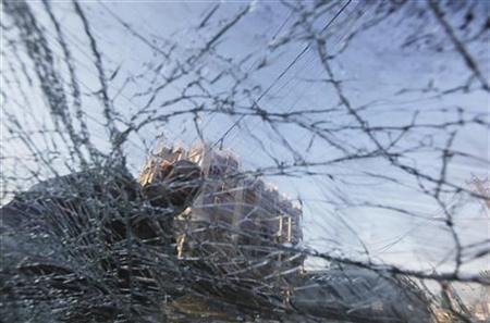 A resident is seen behind the broken windshield of vehicle after a bomb attack in Baghdad's Karrada district, December 31, 2012. REUTERS/Saad Shalash