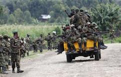 M23 rebel fighters sit on a truck as they withdraw near the town of Sake, 42 km (26 miles) west of Goma in eastern Congo November 30, 2012. REUTERS/James Akena