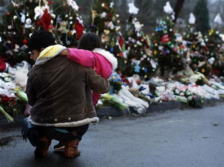 A woman holds a child next to a makeshift memorial for victims who died in the December 14 shootings at Sandy Hook Elementary School, in Newtown, Connecticut December 18, 2012. REUTERS/Shannon Stapleton