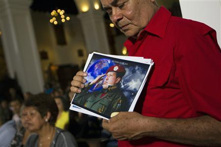 A supporter of Venezuelan President Hugo Chavez holds a picture of him, as he attends a mass to pray for Chavez's health in Caracas December 31, 2012. REUTERS/Carlos Garcia Rawlins